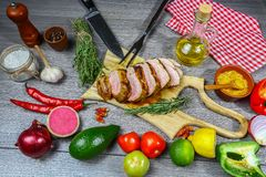 Fresh beef steak and aromatic herbs, spices and vegetables for cooking , on rustic background, top view, frame stock photo