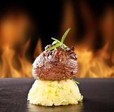 Fresh beef steak on black stone and fire Royalty Free Stock Photo