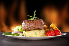 Fresh beef steak on black stone and fire Royalty Free Stock Image