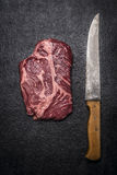 Fresh beef steak with carving knives on dark rustic background top view. Fresh beef steak with carving knives on a dark rustic background top view stock photography