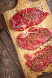 Fresh beef steak and spicel on board. Diagonal vertical Royalty Free Stock Photo