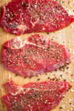 Fresh beef steak and spicel on cutting board. Top view vertical Royalty Free Stock Photography