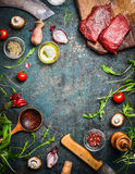 Fresh beef steak, wooden spoon, knife and aromatic herbs, spices and vegetables for cooking , on rustic background, top view. Frame Stock Photo