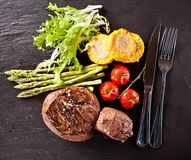 Fresh beef steaks on black stone Royalty Free Stock Images