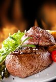 Fresh beef steaks on black stone and fire Royalty Free Stock Image