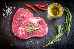 Fresh beef steaks with ingredients on the dark background Royalty Free Stock Photos