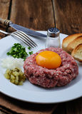 Fresh beef tartar with egg, pickled cucumber and onion. Royalty Free Stock Photo