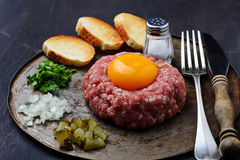 Fresh beef tartar with egg, pickled cucumber and onion. Royalty Free Stock Photos
