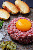 Fresh beef tartar with egg, pickled cucumber and onion. Royalty Free Stock Images