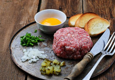 Fresh beef tartar with egg, pickled cucumber and onion. Stock Image
