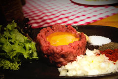 Fresh beef tartar with egg, pickled with spices, onion, ketchup Stock Photos