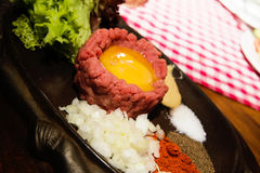 Fresh beef tartar with egg, pickled with spices, onion, ketchup Stock Photo
