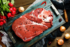 Fresh beef veal meat on rustic tray. Fresh beef veal meat on rustic wooden table with fresh vegetables, top view Royalty Free Stock Image