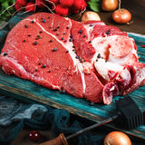 Fresh beef veal meat on rustic wooden table. With kitchen utensils and vegetables, square composition Royalty Free Stock Images