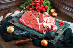 Fresh beef veal meat on rustic wooden table. With kitchen utensils and vegetables, rustic style Royalty Free Stock Photos