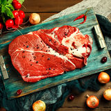 Fresh beef veal meat on rustic wooden table. With kitchen utensils and vegetables, top view Stock Photos