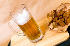 Fresh beer with bread toast. On wood Stock Images