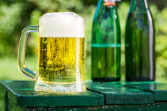 Fresh beer in garden. On old wooden table royalty free stock images