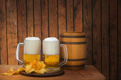 Fresh beer in the glass and chips. Fresh beer in the glass and chips on wooden background royalty free stock photography