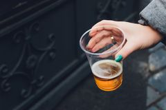 Fresh beer in a plastic cup in the hand. royalty free stock image