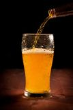 Fresh beer pouring from bottle into glass Royalty Free Stock Photography
