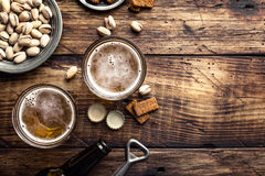Fresh beer. Two glasses of fresh beer and salty snacks on a brown wooden table, top view and space for text stock photography