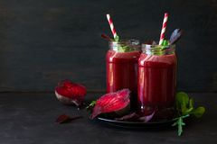 Fresh beetroot smoothie, beet, arugula and lettuce leaves. On dark wooden background stock images