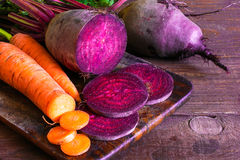 Fresh beets and carrots on wooden background Royalty Free Stock Photography