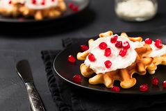Fresh belgian waffles with cream and pomegranate seeds on black background. royalty free stock photos