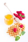 Fresh Belgian waffles with raspberries. And honey on a white background royalty free stock photos