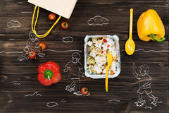 Fresh bell peppers lying near cooked rice. Summer freshness, Top view of bellpeppers lying on the wooden table near foil bowl with cooked rice Royalty Free Stock Image