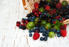 Fresh berries with basket. On a wooden background Stock Photos