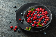 Fresh berries on black background. Fresh berries in a black ceramic bowl on black background Royalty Free Stock Image