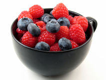 Fresh berries in black cup. Fresh raspberries and blueberries in a black cup on white Stock Photography