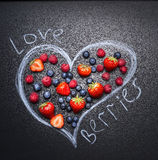 Fresh berries, blueberries, strawberries and raspberries, are laid out in the drawn heart the chalkboard top view. Fresh berries, blueberries, strawberries and Royalty Free Stock Photos