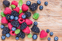 Fresh berries, blueberry, raspberry, blackberry on rustic wood background. Top view copy space Royalty Free Stock Photo