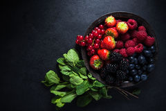 Fresh berries in bowl, antioxidant concept. Fresh berries in rustic bowl, antioxidant concept, food border background Stock Images