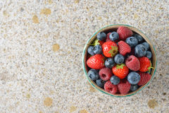 Fresh berries in a bowl. On a brown background Royalty Free Stock Image