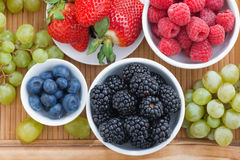 Fresh berries in a bowl and green grapes on wooden tray Stock Photography