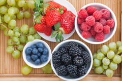 Fresh berries in bowl and green grapes on wooden tray, top view Royalty Free Stock Photos