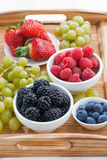 Fresh berries in a bowl and green grapes on wooden tray Royalty Free Stock Image