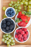 Fresh berries in bowl and green grapes on wooden tray, vertical Royalty Free Stock Image