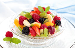 Fresh berries in bowl. Mixed fresh fruits and mint leaves in glass bowl Royalty Free Stock Photos