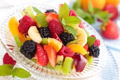 Fresh berries in bowl. Mixed fresh fruits and mint leaves in glass bowl Royalty Free Stock Image