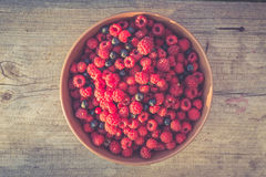 Fresh berries in a bowl. Bowl with raspberries and blueberries over wooden background, top view. Filtered image Stock Photos