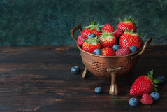 Fresh berries in bowl. Summer berries in bowl on wooden table, strawberry, raspberry and blueberry Stock Images
