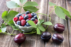 Fresh berries in a bowl on a wooden table. Fresh assorted berries on wooden table in small ceramic dishes Stock Photography