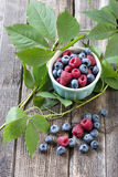 Fresh berries in a bowl on a wooden table. Fresh assorted berries on wooden table in small ceramic dishes Royalty Free Stock Image
