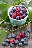 Fresh berries in a bowl on a wooden table. Fresh berries in bowl on Wooden Background, raspberry and blueberry Stock Photo
