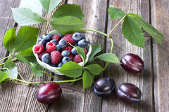 Fresh berries in a bowl on a wooden table Royalty Free Stock Photos